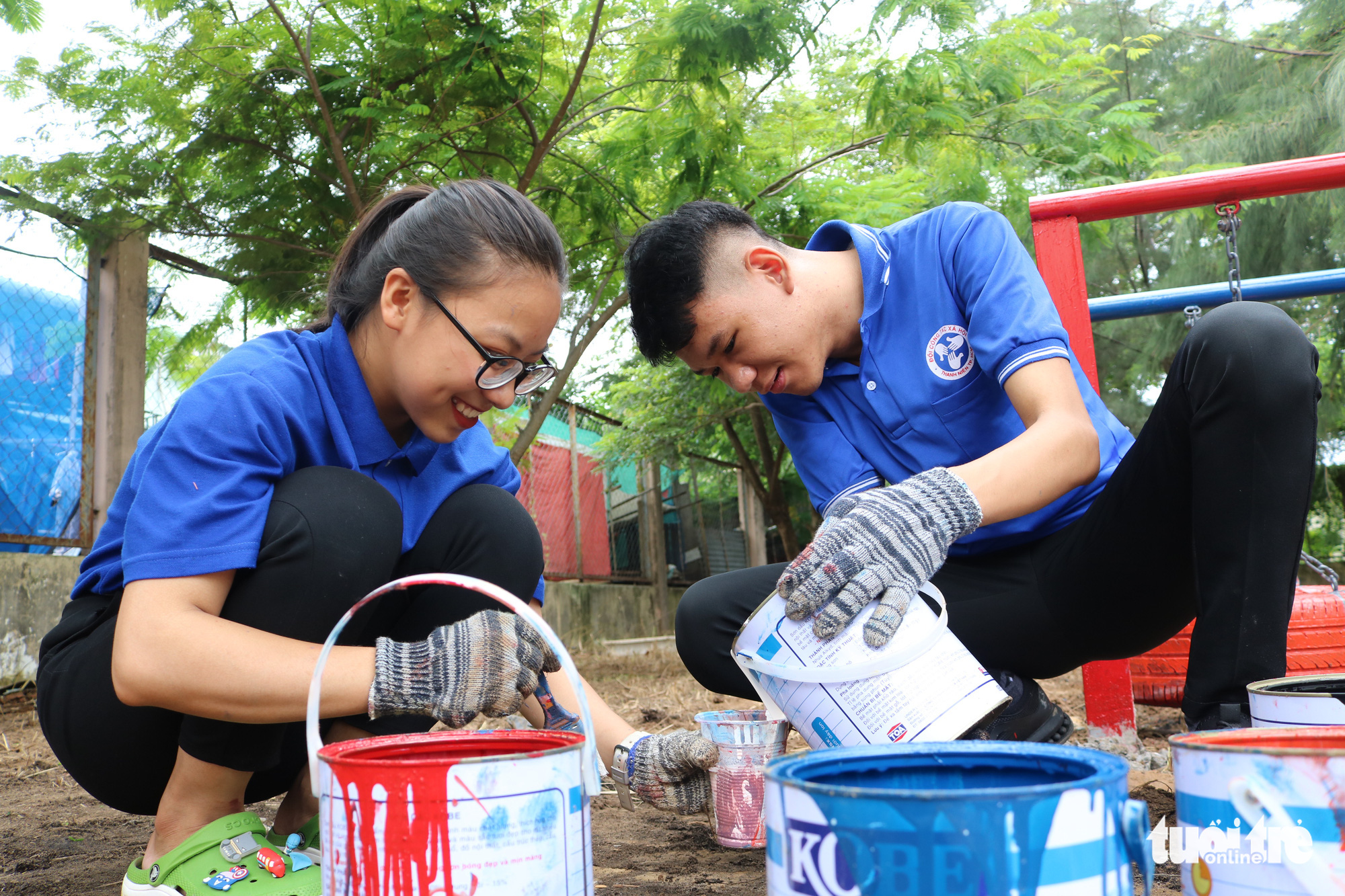 Two volunteers mix paint to make over old car tires for a playground in Nha Be District, Ho Chi Minh City, Vietnam. Photo: Hoang An / Tuoi Tre