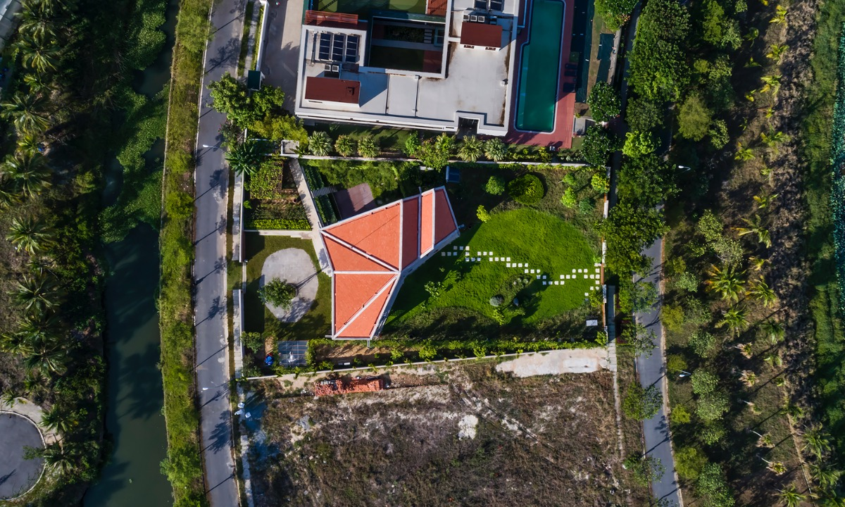 On a 400-meter-square plot in a quiet neighborhood in Da nang, an old couple wanted to build a villa for their five-people family. The land gives a view to a local lake with a large surrounding garden,  so architects designed an L-shaped building with open spaced to take disadvantage of the outdoor greenery.